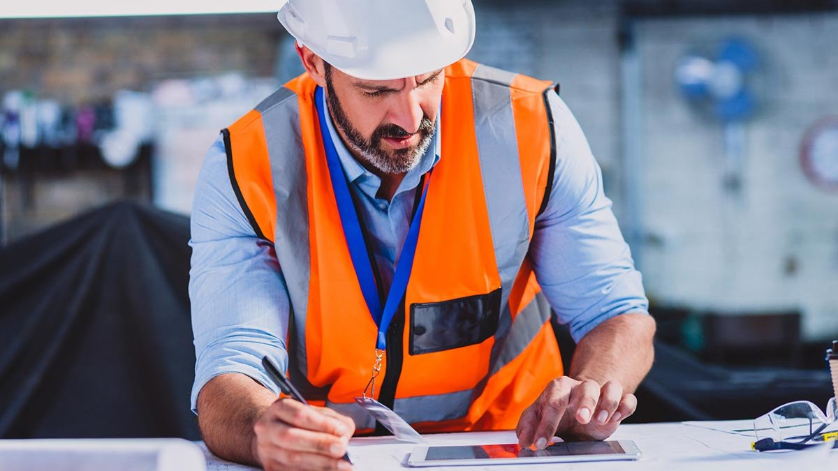 worker referring to plans and tablet device at job site