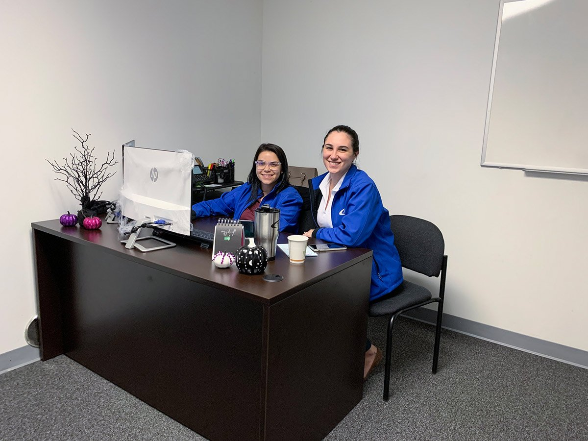 Blue Wave Communications staff members sitting at a desk
