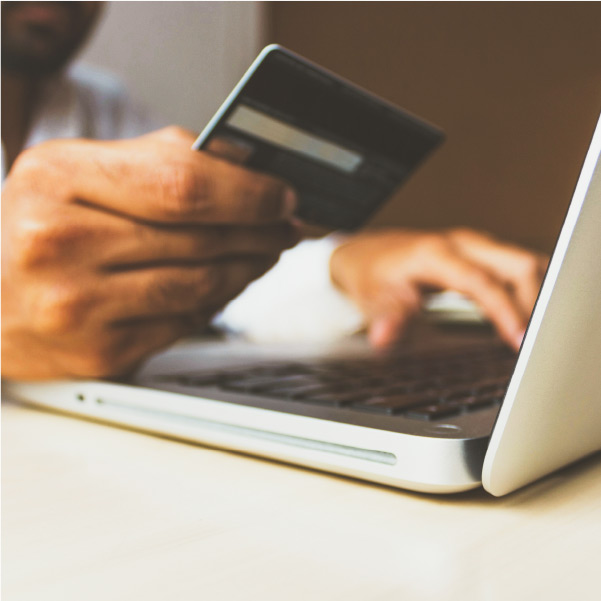 User holding credit card, making an online purchase with a laptop.