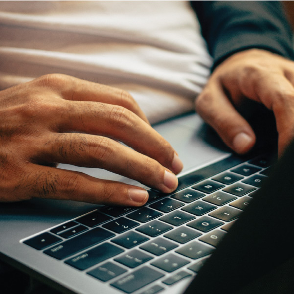 Close up of user's hands operating a laptop.