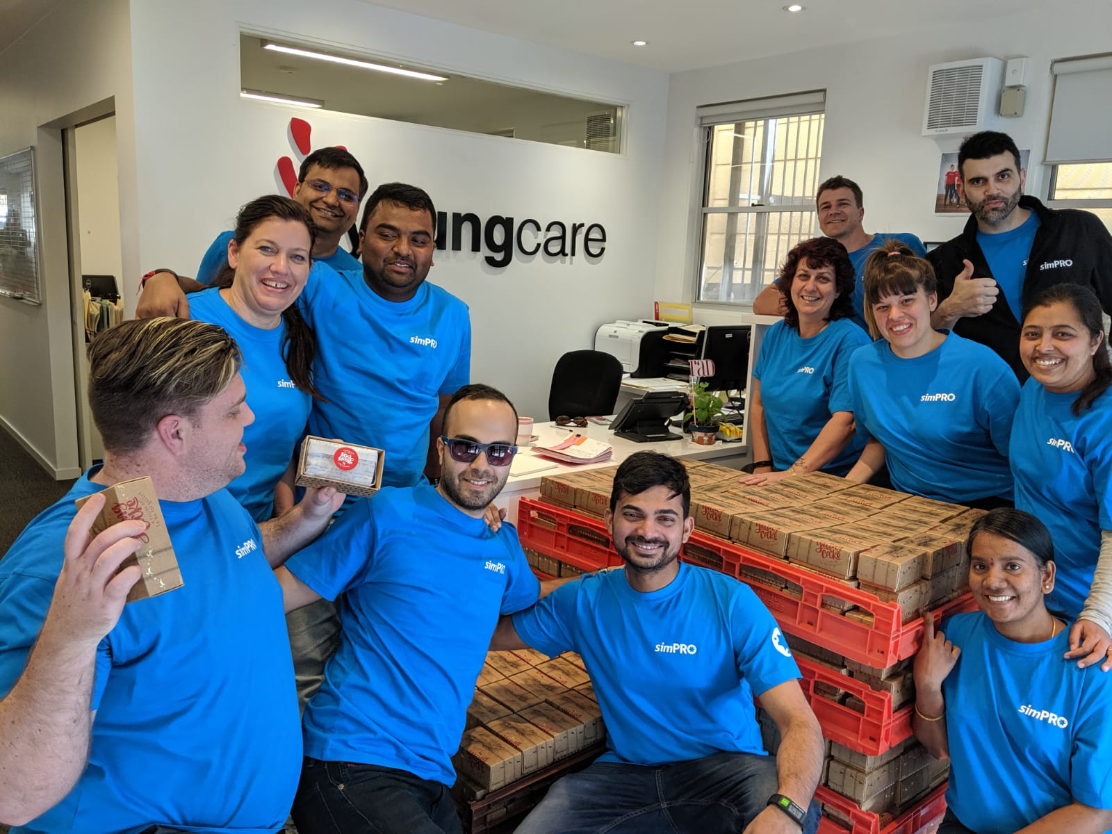 simPRO employees celebrating succes after wrapping cakes for Youngcare